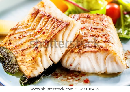 Close-up of two plates with seafood and vegetables served by an experienced chef Stock photo © Kzenon