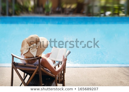 Stock photo: Young woman relaxing on the deckchair by the swimming pool in sp