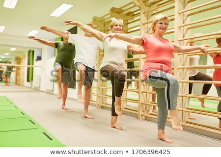 Seniors training fitness and coordination with gymnastics in nursing home Stock photo © Kzenon