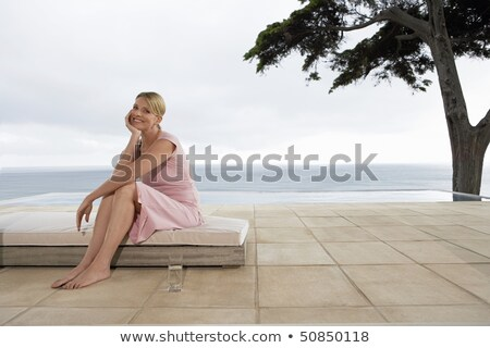 Adult contented woman on terrace at resort Stock photo © dash