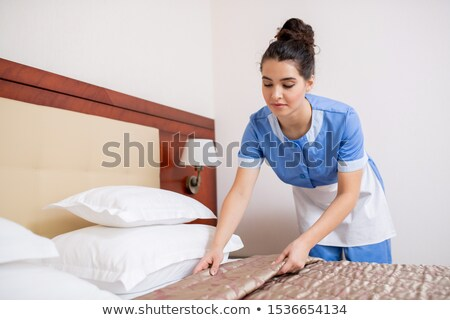 Pretty young brunette chamber maid in blue uniform making bed in hotel room Stock photo © pressmaster