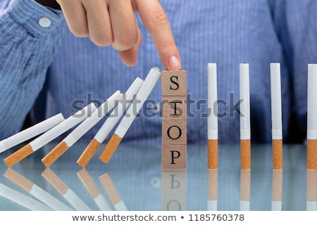 Person Stopping Cigarette From Falling With Wooden Blocks Stock photo © AndreyPopov