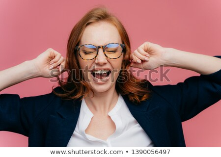 Horizontal shot of ginger woman in formal clothing, demonstrates gesture of ignore, plugs ears, shou Stock photo © vkstudio