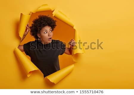 Photo of scared young woman expressing surprise and looking aside Stock photo © deandrobot