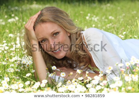 Woman lying in a grassy field Stock photo © photography33