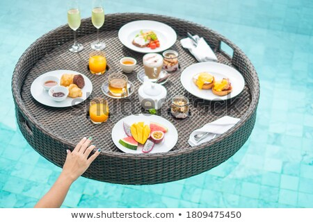 Woman eating bread at a poolside Stock photo © photography33