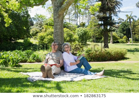 mature couple leaning on tree trunk stock photo © photography33