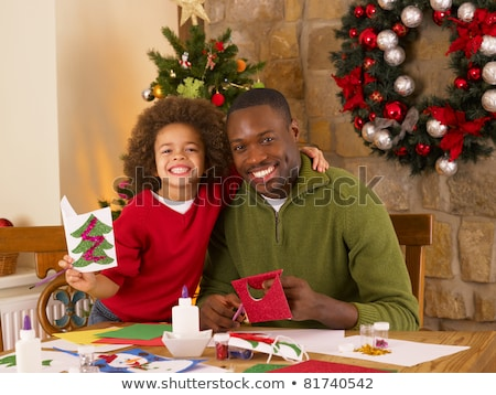 african american father and mixed race son making christmas card stock photo © monkey_business