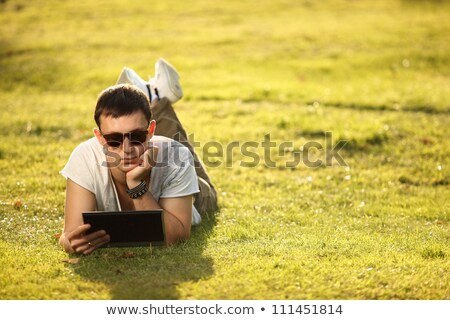 handsome man lying on the lawn with tablet stock photo © stockyimages