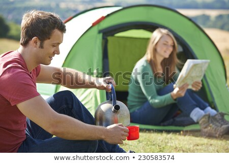 couple making hot drink whilst camping in countryside stock photo © highwaystarz