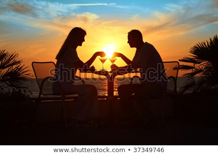 Female and man's silhouettes on sunset sit at table with two gla Stock photo © Paha_L