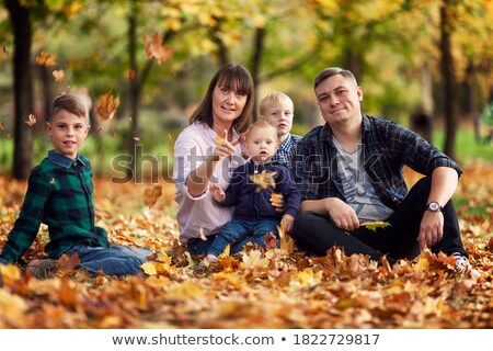 mother and child sit among fallen leaves Stock photo © Paha_L
