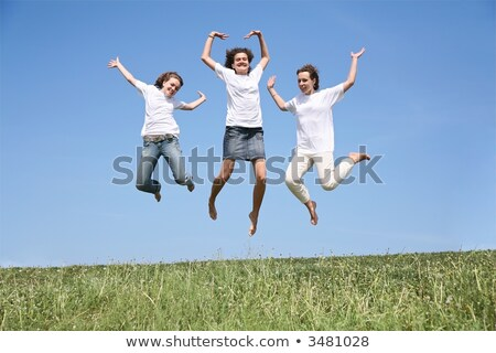 Three girlfriends in white T-shorts jump simultaneously Stock photo © Paha_L