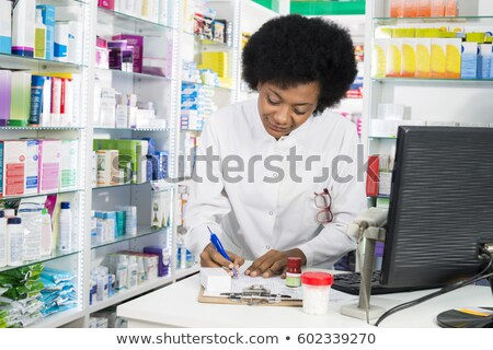 Pharmacist black woman with medicine at counter in pharmacy Stock photo © vectorikart