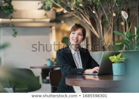 Woman working on laptop in green office Stock photo © IS2