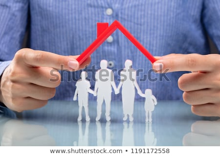 Businesswoman Protecting Family Figures With Red Roof Stock photo © AndreyPopov