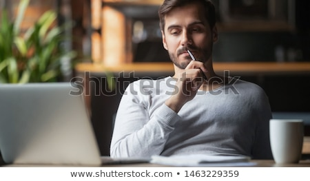 A young man sits at a table in the office and holds documents and a pen in his hands. Stock photo © Traimak
