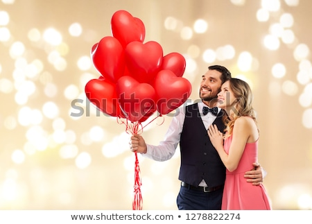 happy couple with balloons over party lights stock photo © dolgachov