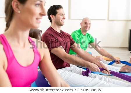 man performing foot exercises with thera band stock photo © kzenon