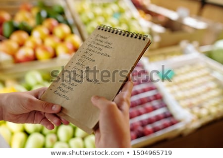 Notepad with list of products to buy in supermarket held by youthful girl Stock photo © pressmaster