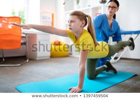 physical therapist gently helping girl stretching her leg stock photo © andreypopov