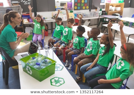 Front view of caucasian teacher teaching about green energy and recycle to attentively students at s Stock photo © wavebreak_media
