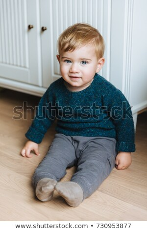 Vertical portrait of infant sits on floor near cupboard, looks with warm blue eyes. Indoor shot of h Stock photo © vkstudio