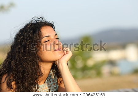 Brunette relaxed female with closed eyes, feels enjoyment as stands alone on seashore, has perfect b Stock photo © vkstudio
