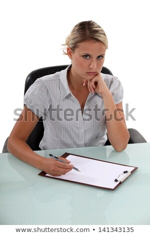 Standoffish woman writing on a clipboard Stock photo © photography33
