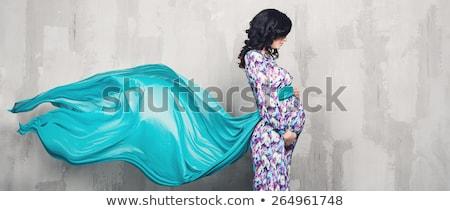 Dark-haired pregnant woman touching belly Stock photo © konradbak