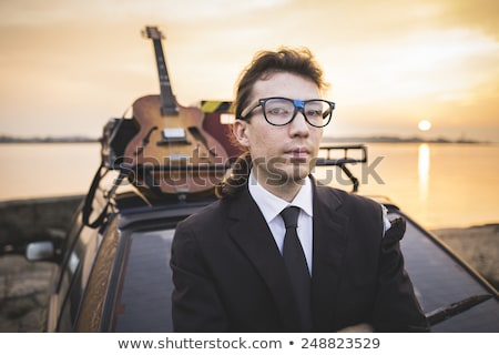 Hipter in glasses and his guitar on car rack stock photo © Kor