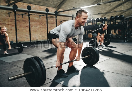 Man with barbell during workout Stock photo © LightFieldStudios