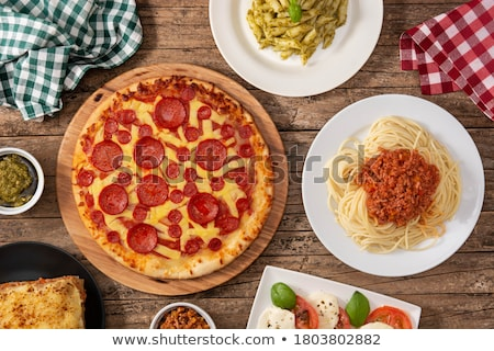 Italian food background with pizza, raw pasta and vegetables on wooden table Stock photo © dash