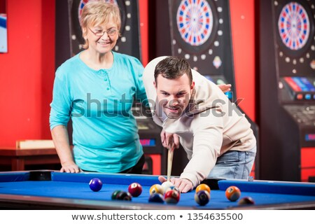 Mother looking at her son playing billiard Stock photo © Kzenon