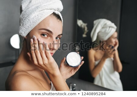 Photo of seductive woman wrapped in towel applying cream at face Stock photo © deandrobot