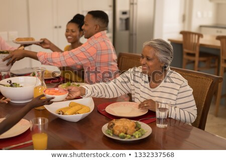 side view of a woman passing food to man on dining table at home Stock photo © wavebreak_media