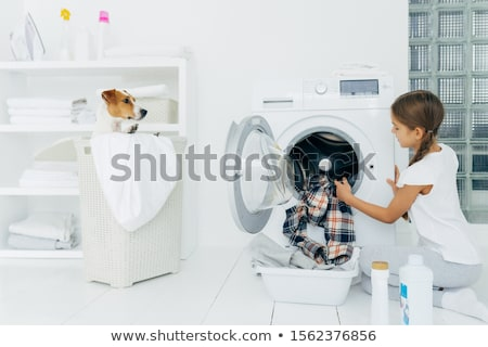 Busy child does laundry work, empties washing machine, cleaned clothes in basin uses detergents, lit Stock photo © vkstudio