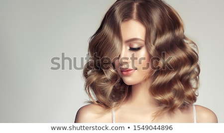 Photo of pleasant looking woman with curly hair, smiles happily, holds modern cell phone for chattin Stock photo © vkstudio