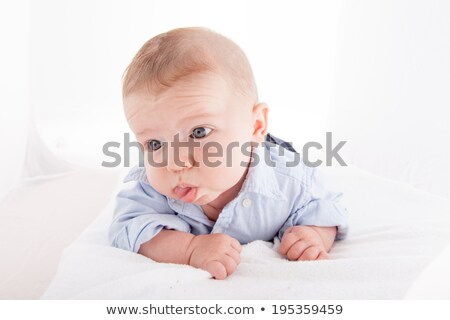 Baby boy lying on the bed and sticking his tongue out Stock photo © bmonteny