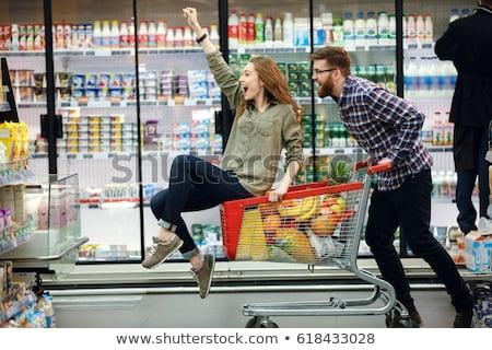 Happy woman riding by shopping trolley. Stock photo © RAStudio