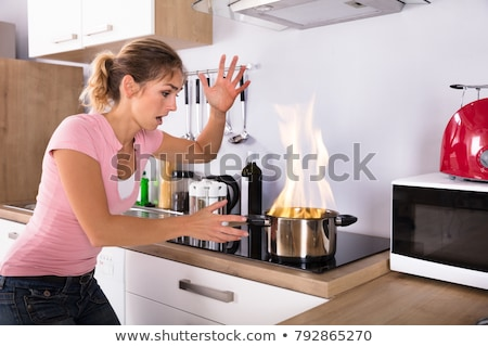 Young Woman Looking At Burning Cooking Pot Stock photo © AndreyPopov