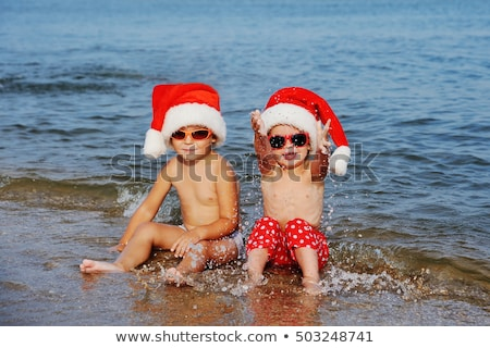 two boys are celebrating christmas on the beach stock photo © galitskaya