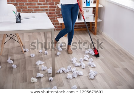 Female Janitor Sweeping Crumbled Paper On Floor Stock photo © AndreyPopov
