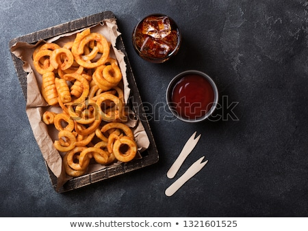 Curly fries fast food snack in wooden box with glass of cola on rusty stone kitchen background. Unhe Stock photo © DenisMArt