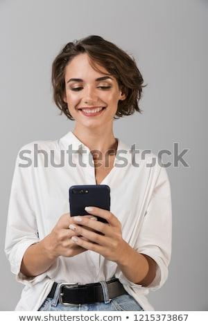 Gelukkig jonge zakenvrouw poseren mobiele telefoon Stockfoto © deandrobot
