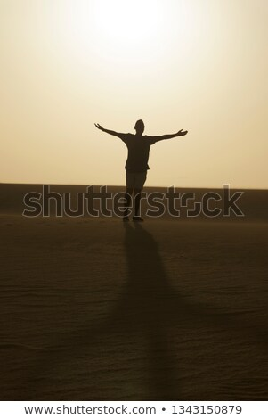man with his arms open in the air, in the desert Stock photo © nito