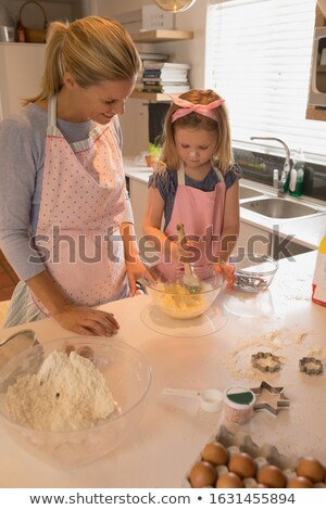 Front view of happy mother with her daughter baking cookies in kitchen at home Stock photo © wavebreak_media
