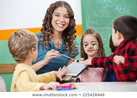 Music teacher with students in class on the xylophone Stock photo © Kzenon