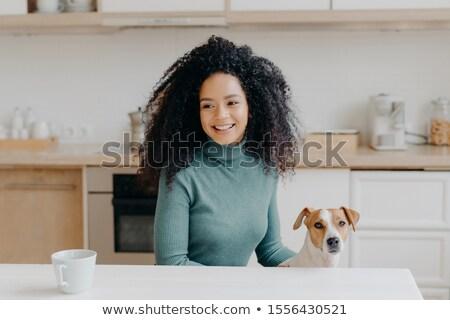 Happy dark skinned girl looks thoughtfully away, has pleasant smile, dressed in casual wear, drinks  Stock photo © vkstudio