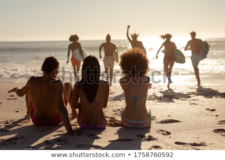Rear view of multi ethnic group of friends holding surfboard and running toward sea at beach on a su Stock photo © wavebreak_media